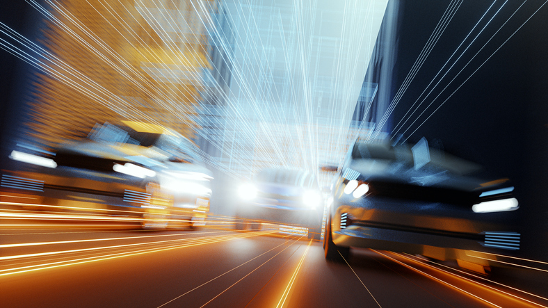 blurry low angle view of cars speeding down a city roadway